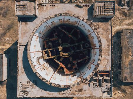 Aerial top down view of abandoned and ruined Nuclear Power Plant in Shelkino, Crimea. Large USSR industrial construction with round tower of atomic reactor, drone shot. Stock Photo