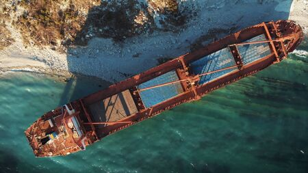 Cargo ship run aground at sea coastline near Novorossiysk and Gelendzhik. Shipwreck accident of nautical vessel after huge sea storm, aerial view from drone. Stock Photo