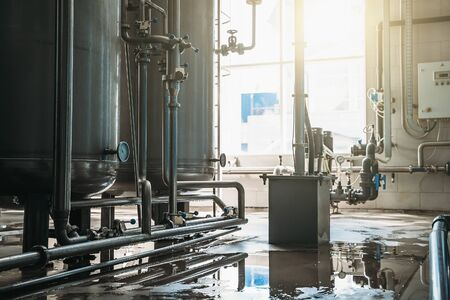 Drinking water factory or plant production, industrial interior. Large metal tanks for filtering and potable water treatment. Stock Photo