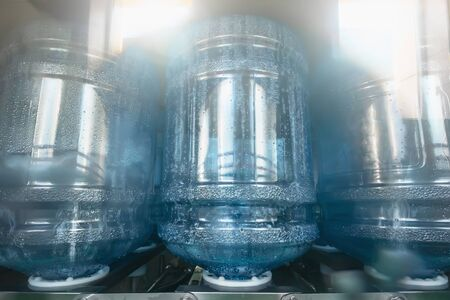 Washing, cleaning and disinfection of inner surface of reusable plastic bottles for drinking water in special machine at water factory, close up.
