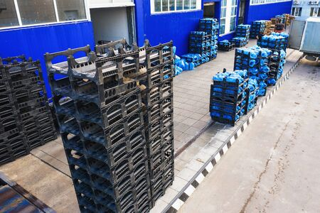 Aerial view of freight warehouse of drinking water plant or factory, racks with plastic bottles or gallons ready for loading at trucks.