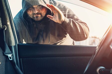 Criminal person in hood looks inside car through glass or window, Robber or car theft concept. Reklamní fotografie