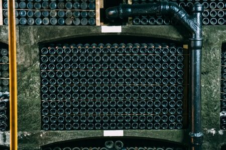 Wine bottles in winery cellar, many alcohol in underground storage, close up.