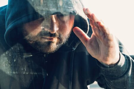 Criminal person in hood looks inside car through glass or window, Robber or car theft concept. Stock Photo