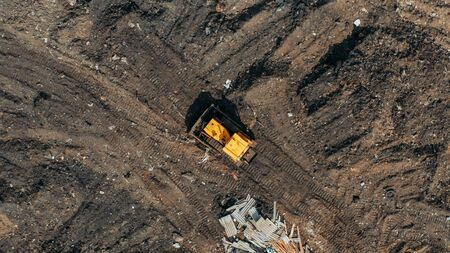 Yellow excavator or bulldozer on city dump yard, aerial or top view from drone. Stock Photo