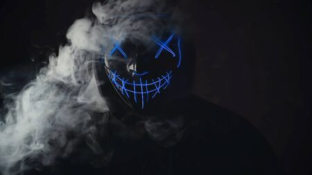 Man with lighting neon glow mask in hood and vape vapour from mask on black background. Halloween and horror concept. Stock Photo