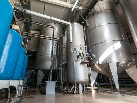 Drinking water factory or plant production, industrial interior. Large metal tanks for filtering and potable water treatment from well. Stock Photo