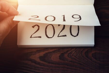New Year 2020 coming concept. Male fingers flips notepad or calendar sheet. 2019 is turning, 2020 is opening, top view, toned