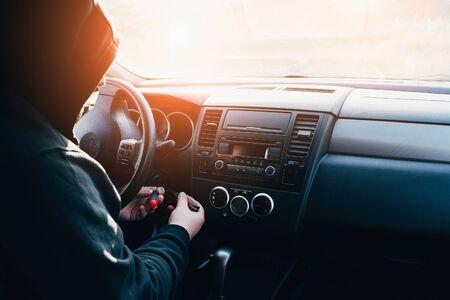 Krimineller in Motorhaube versucht, Auto zu stehlen, bricht schlüsselloses Schloss, um Automotor zu starten, getönt