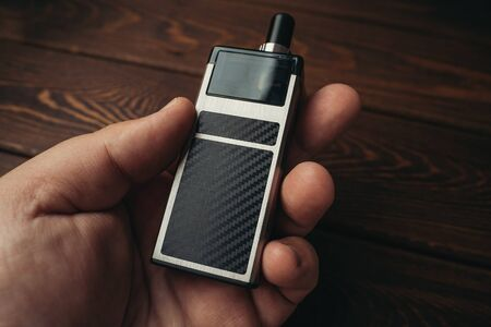 Vape pod in male hand or pod mod close up - newest generation of vaping products. Stock Photo