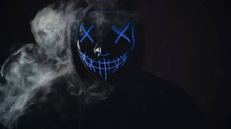 Man with angry and scary lighting neon glow mask in hood on black background with smoke. Halloween and horror concept.
