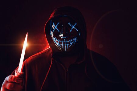 Man with knife in hand and angry and scary lighting neon glow mask in hood on dark red background. Halloween and horror concept.