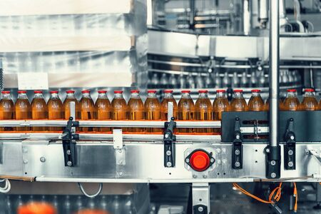 Conveyor belt, juice in glass bottles in automated machine equipment on beverage factory, close up.