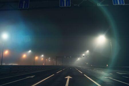 Night foggy street or wet asphalt road and city illumination lights in autumn mist, horror atmosphere, toned