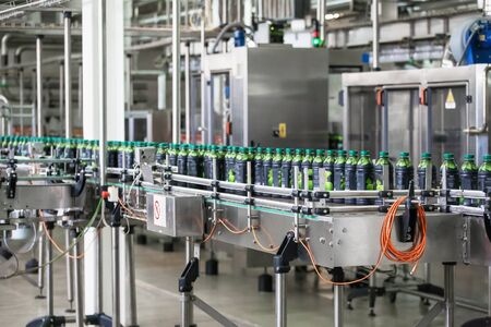 Conveyor line with plastic bottles of juice at modern factory equipment. Beverage manufacturing plant interior inside.