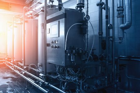 Beverage industrial factory with automated machine equipment in sun light, blue toned