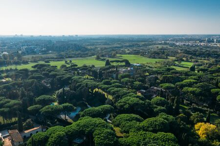 Aerial view of ancient Via Appia Antica with green trees, meadows, houses and pathways in Rome, Italy.