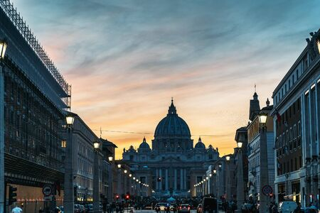 Saint Peter Basilica and Street Via della Conciliazione in evening city lights at sunset, Rome, Italy.