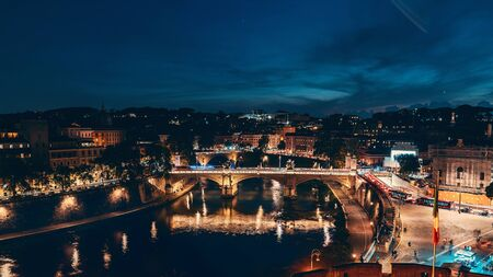 St Angel Bridge or Ponte Sant Angelo or Aelian Bridge on Tiber river at night with city illumination in Rome, Italy, view from above.