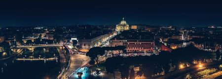 St Angel Bridge on Tiber river and St. Peter Basilica in Vatican City at night with city illumination in Rome, Italy, view from above, panorama.