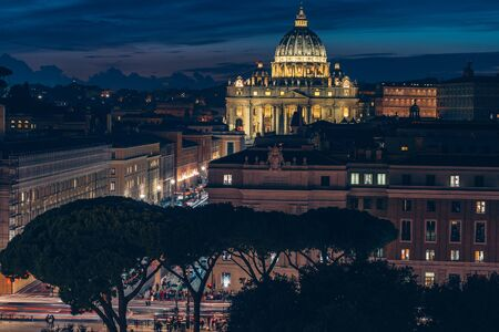 Illuminated St. Peter Basilica dome in Vatican City over other buildings at night in Rome, Italy, view from above.