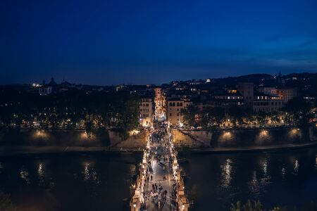 Bridge to Castle of Holy Angel with people at night in Rome historic centre, view from above.