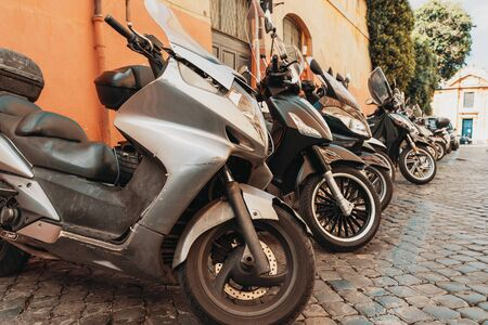 Many motor scooters parked on old Rome street, Italy .