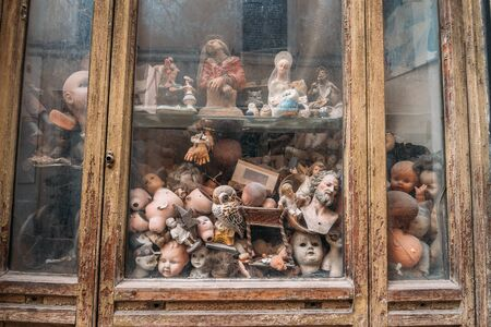 Abandoned dolls workshop, many plastic parts of baby dolls behind dirty glass.