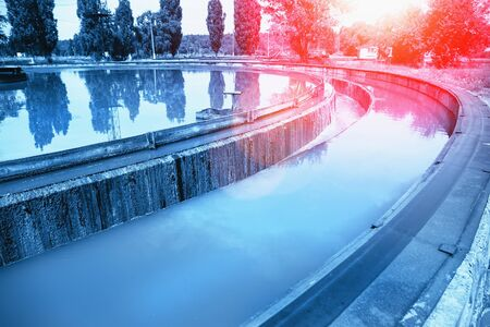 Tank or reservoir for aeration and purification or cleansing sewage liquid with sludge in modern wastewater treatment plant, blue toned with red flare.