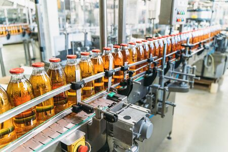 Conveyor belt, juice in bottles on beverage plant or factory interior, industrial production line, selective focus