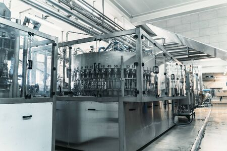 Industrial machine in beverage plant or factory interior, industry equipment, toned