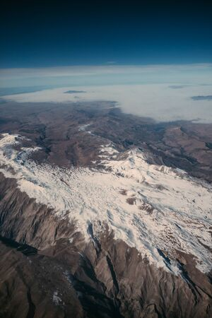 Beautiful nature mountain landscape with snow from airplane window.