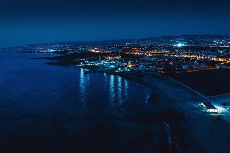 Aerial panoramic view of Paphos, Cyprus seaside from above at night from drone. Beautiful evening mediterranean seascape with illuminated buildings and reflections of lights in sea water.