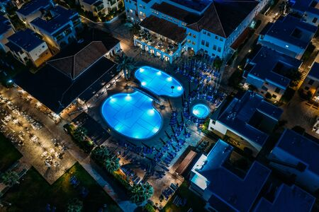 Aerial top view of illuminated pool in modern mediterranean hotel at night. Stok Fotoğraf