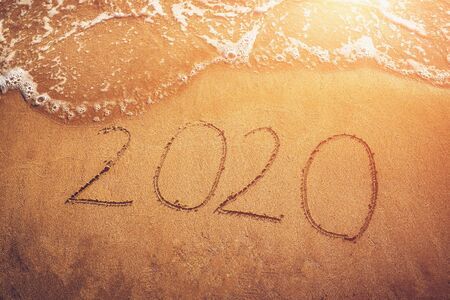 Happy New Year 2020, handwritten numbers on sandy beach with sea waves at sunset light. New Year, travel and new beginnings concept. Stok Fotoğraf