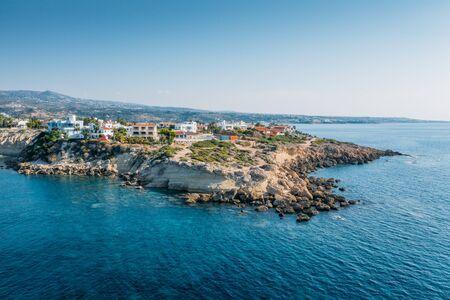 Vista aerea della bellissima scogliera naturale con ville o case vicino alla spiaggia di Coral Bay a Paphos, Cipro. Foto drone di sfondo marino mediterraneo.