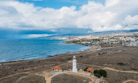 Old lighthouse on Mediterranean Sea shore in Paphos, Cyprus, aerial view from drone. Famous place in Paphos coastline. Stok Fotoğraf