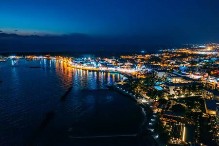 Aerial view of Paphos embankment or promenade at night with reflection of city lights in sea water. Famous Cyprus mediterranean resort.