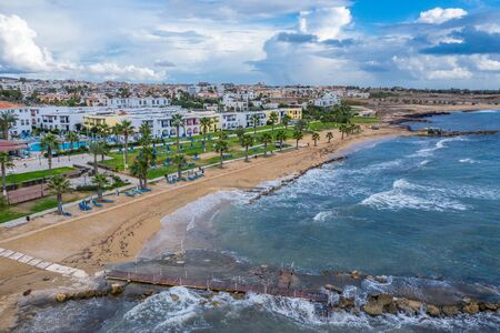 Paphos embankment or promenade, Cyprus, with sandy beach, green palm trees and lawns and small houses on first coastline, aerial view from drone.
