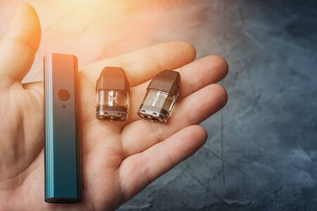 Vape pod system or pod mod with changeable cartridges close up in male hand.