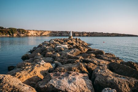 Mediterranean sea and marina or stone pier or breakwater in bay at sunset.