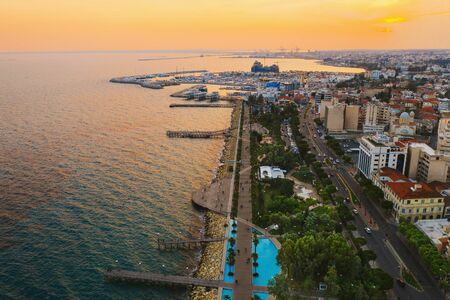 Limassol promenade at sunset, Cyprus. Aerial panoramic view of evening Limassol with Molos Park from above, drone photo. Mediterranean evening landscape, beautiful Cyprus resort for vacation.