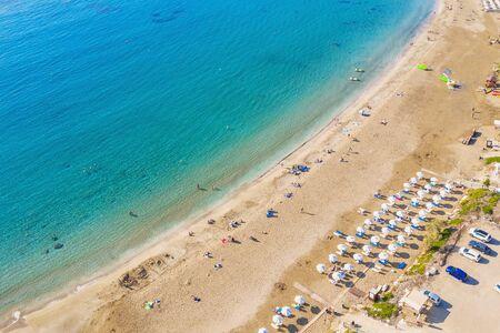 Vista aerea della bellissima spiaggia di corallo a Paphos con acqua di mare azzurra, Cipro. Costa sabbiosa con ombrelloni, lettini, persone e mare limpido.