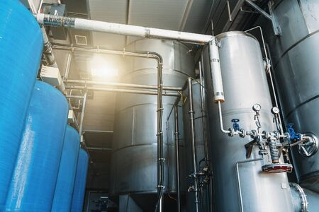Large reservoirs and tanks and pipes in modern water production plant or factory. Industrial interior background.