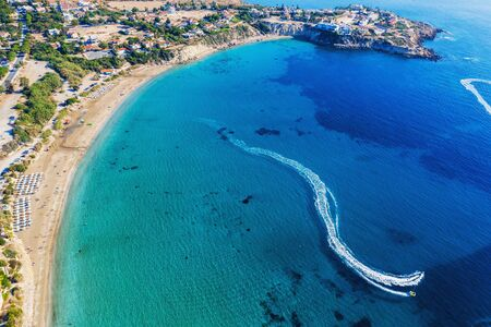 Cyprus landscape. Aerial panoramic view of Coral bay beach with jet ski and people having fun. Mediterranean vacation and travel concept.