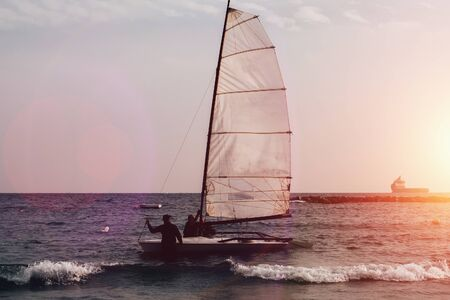 Boat with sail and silhouettes of people in sea water at sunset. Outdoor vacation in mediterranean resort.