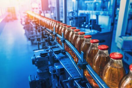 Conveyor belt, factory interior in blue color and bottles with juice, industrial production line, toned