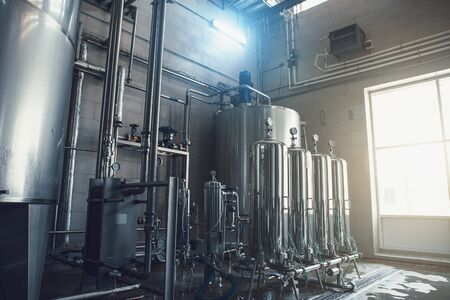 Drinking water factory production, industrial interior. Large metal tanks for filtering and potable water treatment.
