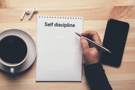 Selbstdisziplin - Text auf Notizblock, weibliche Hand mit Stift bereit, Liste zu schreiben. Standard-Bild
