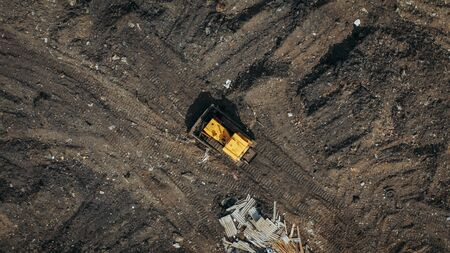 Aerial top view of a construction site or country dump with yellow excavator or bulldozer, heavy equipment, drone photo. Stok Fotoğraf